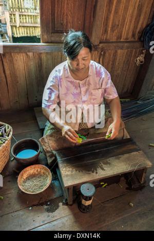 Woman making thread from lotus stalks, Inle Lake, Myanmar - Stock Photo