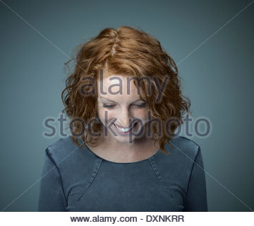 Portrait of smiling redheaded woman looking down - Stock Photo