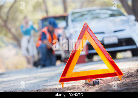 Warning triangle on road with mechanic in background - Stock Photo