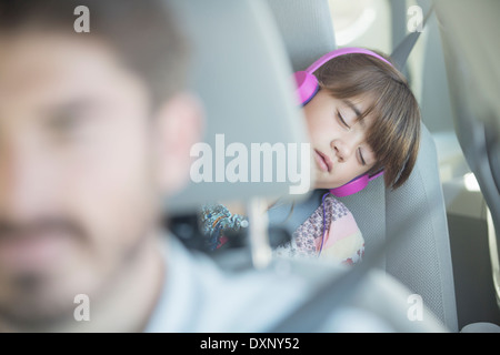 Girl with headphones sleeping in back seat of car - Stock Photo