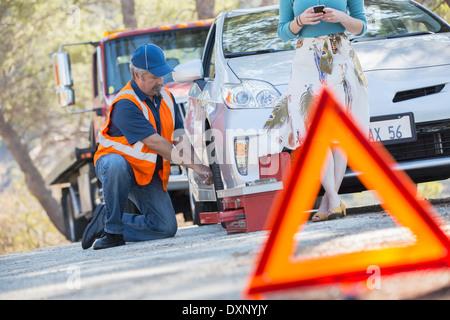 Roadside mechanic changing tire behind warning triangle - Stock Photo