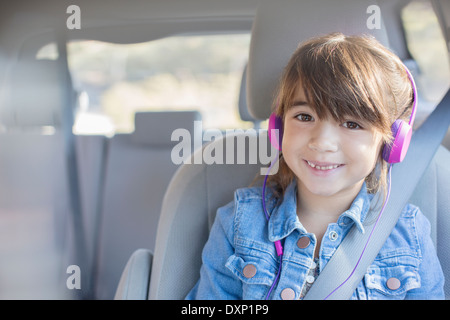 Portrait of smiling girl with headphones in back seat of car - Stock Photo