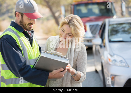 Roadside mechanic and woman reviewing paperwork - Stock Photo