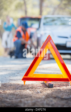 Roadside mechanic helping woman behind warning triangle - Stock Photo