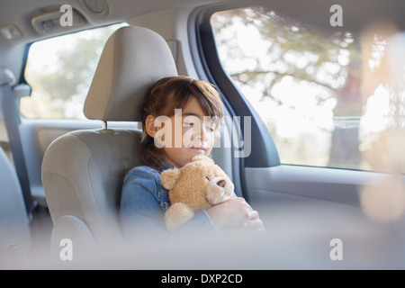 Girl with teddy bear sleeping in back seat of car - Stock Photo