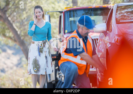Roadside mechanic fixing flat tire for woman on cell phone - Stock Photo