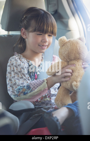 Girl with teddy bear in back seat of car - Stock Photo