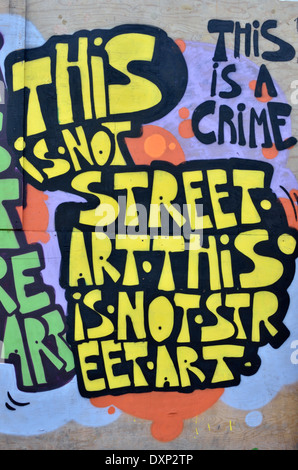 Graffiti on a wall reading: 'This is not sreet art. This is a crime', London, UK - Stock Photo