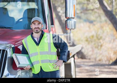 Portrait of confident roadside mechanic leaning on truck - Stock Photo