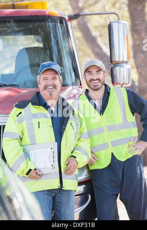 Portrait of confident roadside mechanics - Stock Photo