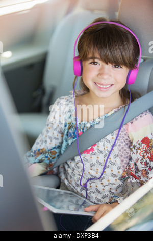Portrait of happy girl with headphones using digital tablet in back seat of car - Stock Photo