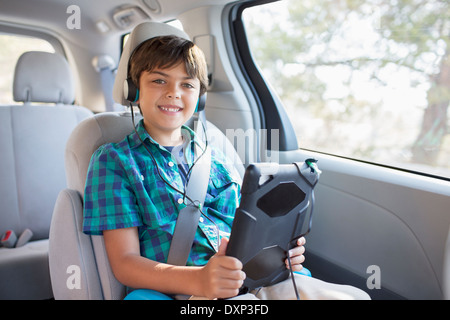 Portrait of happy boy with headphones using digital tablet in back seat of car - Stock Photo