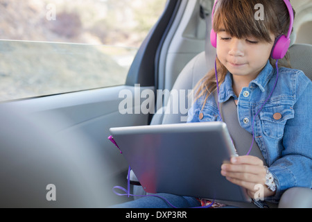 Girl with headphones using digital tablet in back seat of car - Stock Photo