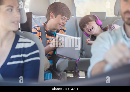 Happy brother and sister using digital tablet in back seat of car - Stock Photo