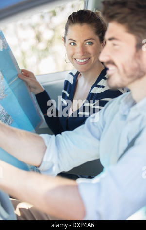 Happy couple with map inside car - Stock Photo