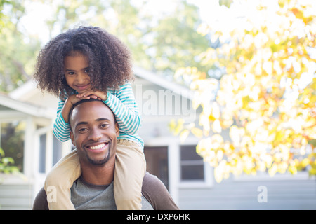 Portrait of happy father carrying daughter on shoulders - Stock Photo