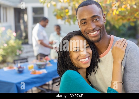 Portrait of happy couple near patio table - Stock Photo