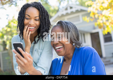Mother and daughter looking at cell phone and laughing
