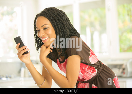 Happy woman text messaging with cell phone - Stock Photo