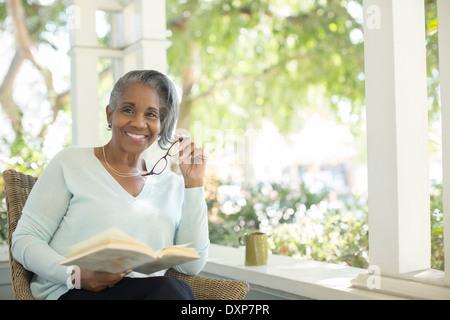 Portrait of smiling senior woman reading book on porch - Stock Photo