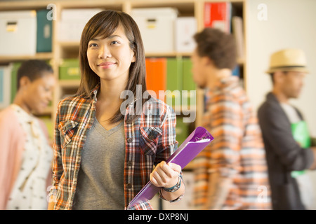 Portrait of confident casual businesswoman with co-workers passing in background - Stock Photo