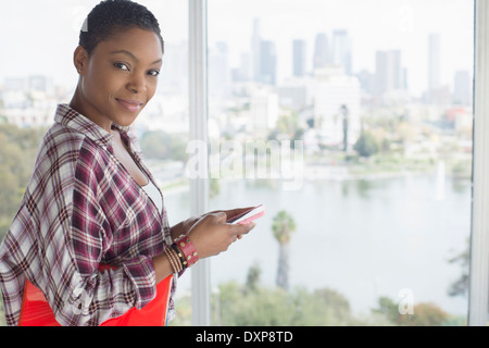 Portrait of confident casual businesswoman holding cell phone at urban window - Stock Photo
