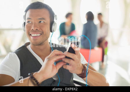 Casual businessman listening to music on headphones with mp3 player - Stock Photo