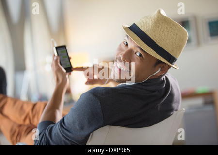 Portrait of confident man in fedora listening to music on headphones with mp3 player - Stock Photo