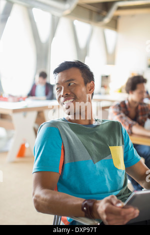 Happy casual businessman looking over shoulder in office - Stock Photo