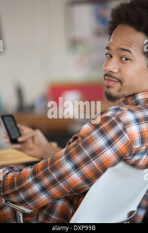 Portrait of confident man text messaging with cell phone - Stock Photo