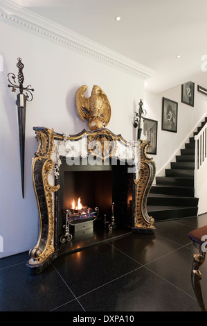 Gilt empire style fireplace by Nicholas Haslam in hallway with black floor tiles - Stock Photo
