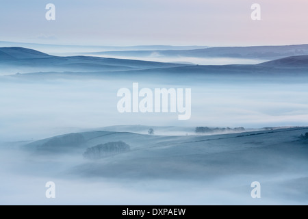 Dawn mists in the Hope Valley. Taken from Mam Tor looking over Castleton towards Shatton and Abney Moors. Peak District. - Stock Photo