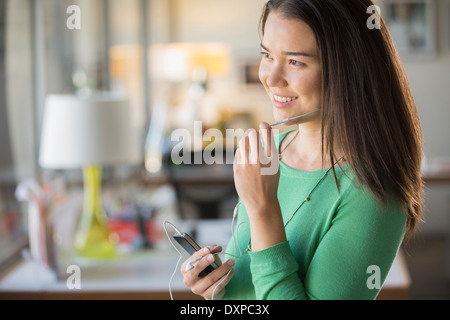 Smiling businesswoman using hands-free device with cell phone in office - Stock Photo