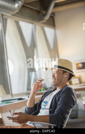 Casual businessman using hands-free device with cell phone in office - Stock Photo