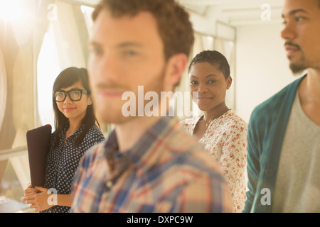 Portrait of smiling casual businesswoman with co-workers - Stock Photo