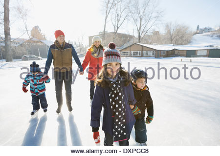 Family ice-skating on outdoor rink together - Stock Photo