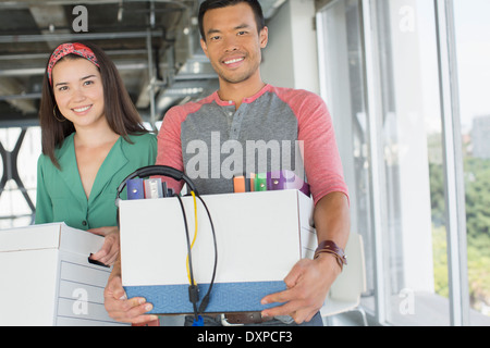 Portrait of happy casual business people carrying boxes of belongings in office - Stock Photo