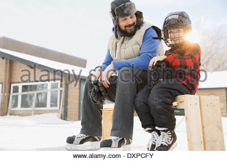 Father and son in ice hockey equipment sitting on bench - Stock Photo