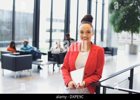 Pretty young woman holding a laptop standing by a railing looking at camera smiling. Young African-American businesswoman. - Stock Photo