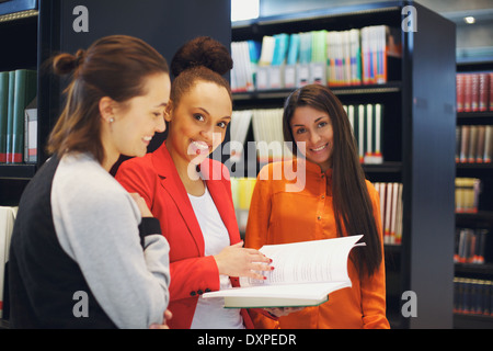 Portrait of group of female students standing in library sharing their study notes. College students preparing for - Stock Photo