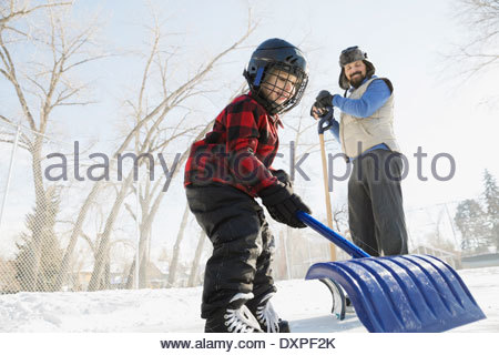 Father and son clearing snow from skating rink with shovels - Stock Photo