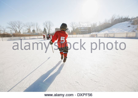 Rear view of ice hockey player skating on rink - Stock Photo