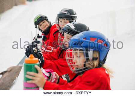 Ice hockey players with water bottles on rink - Stock Photo