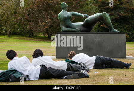 Reclining schoolboys drawing a bronze sculpture of a reclining female figure by Henry Moore in Kew Gardens London - Stock Photo