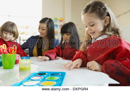 Teacher with girls finger painting in art class - Stock Photo