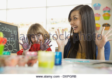 Teacher with girl finger painting in art class - Stock Photo