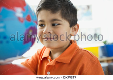 Smiling boy looking at globe in school - Stock Photo
