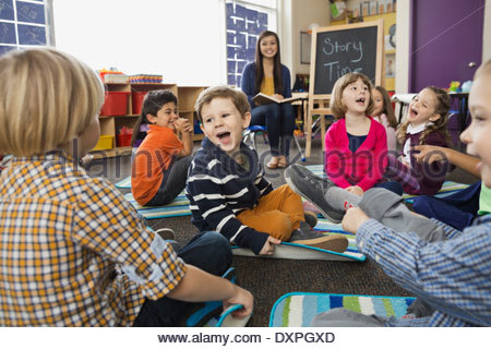 Cheerful students with teacher in elementary school during Story Time - Stock Photo