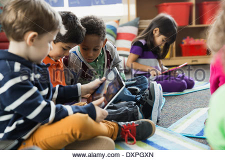 Boys using digital tablet together in elementary school - Stock Photo