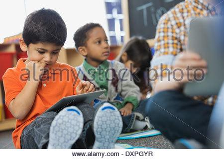 Boy using digital tablet in school - Stock Photo